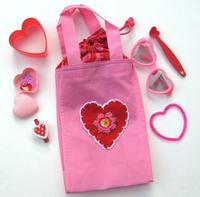 a heart on a pink bag with smaller hearts surrounding it