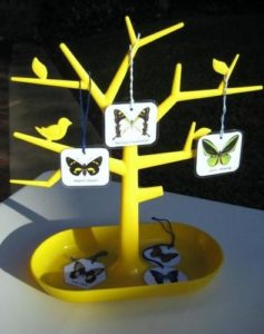 A plastic yellow tree with cards hanging from it